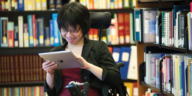 Girl in a wheelchair in the library using a computer tablet.
