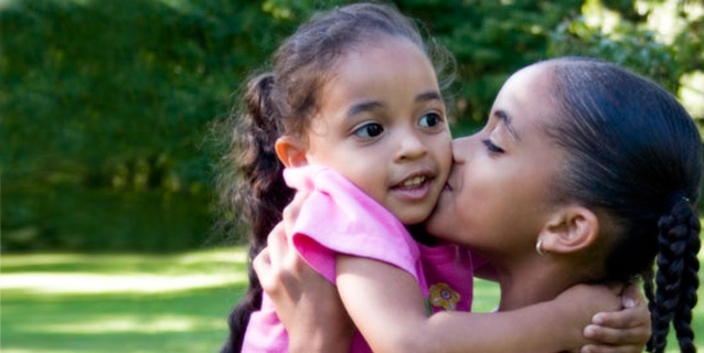 Young woman holding up a little girl and kissing her on the cheek.