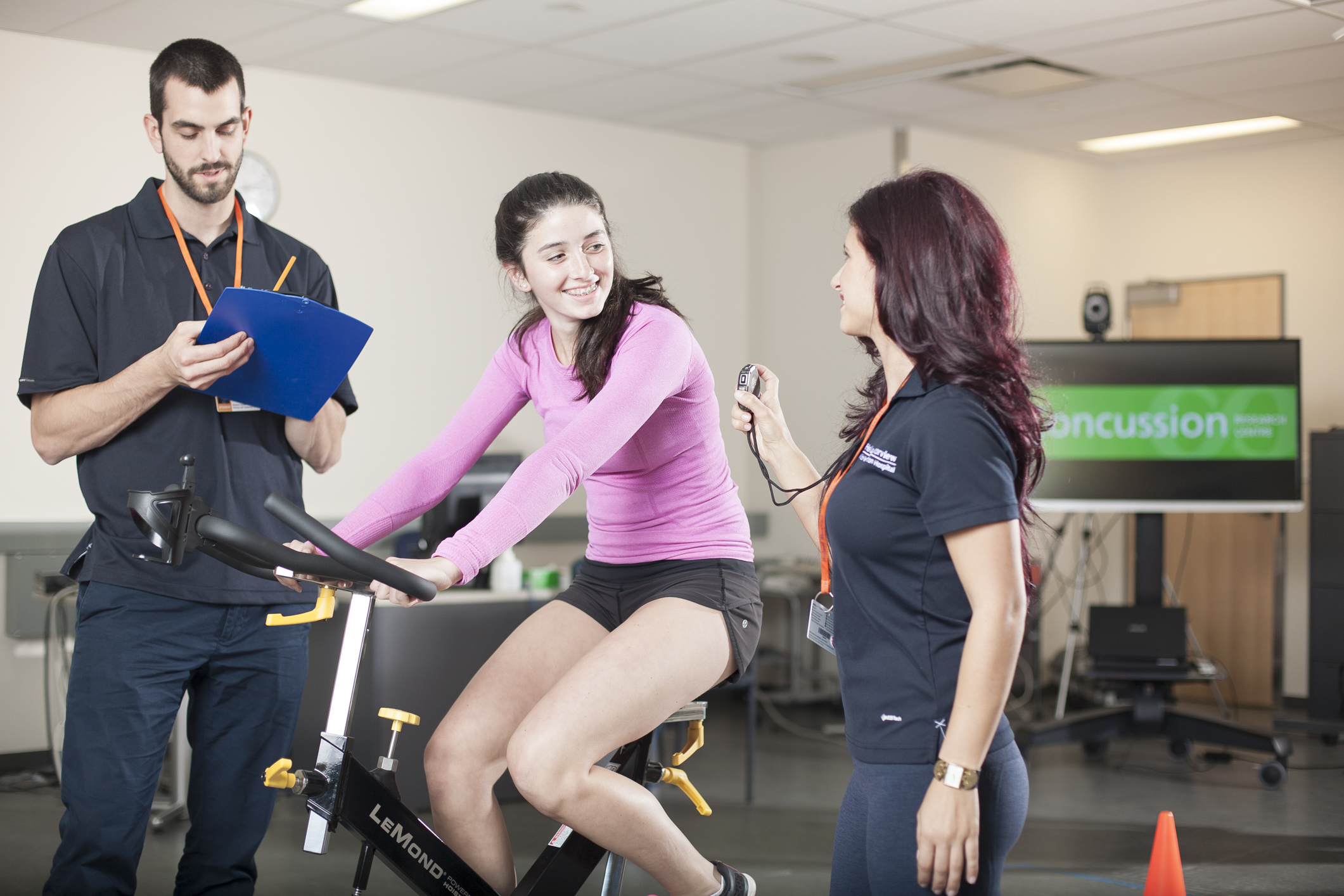 Girl riding exercise bike while a man and woman observe