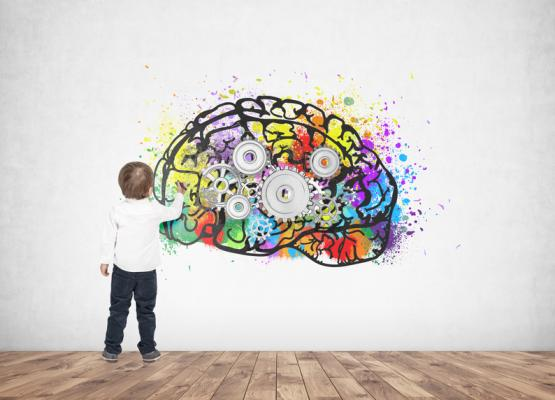 Image of small boy painting a colourful brain