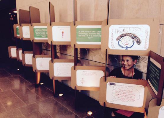 Woman crouches behind display of children's drawings