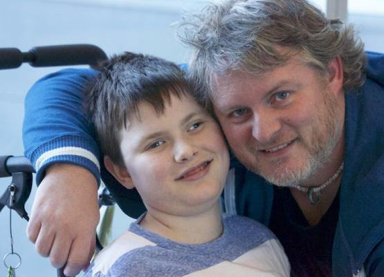 Dad with arm around school-aged son in wheelchair