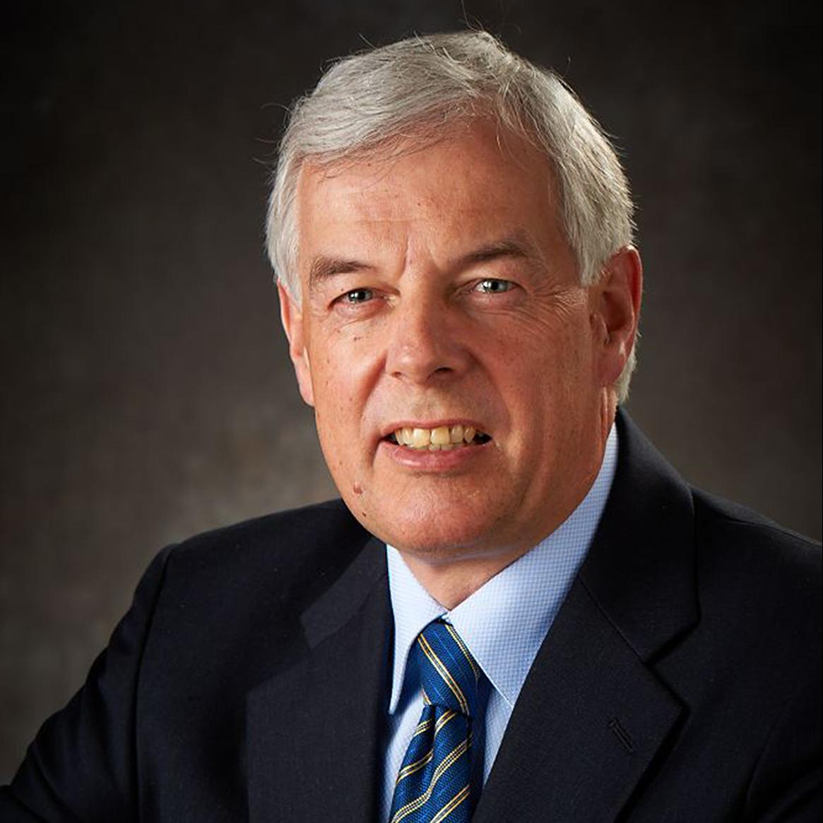 Man with gray hair wearing a dark blazer, light blue shirt, and a blue-striped tie