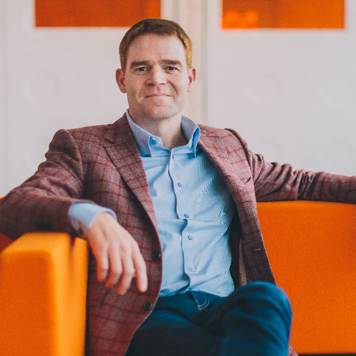 Man with short brown hair wearing a light blue shirt and plaid blazer sitting on a bright orange couch.