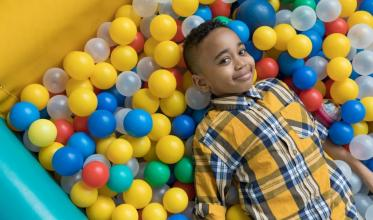Young boy laying in ball pit