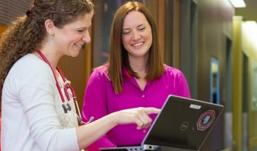 Two staff members looking at a laptop