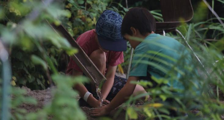 Two kids tending to the garden