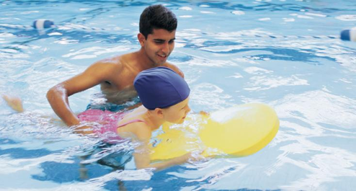 Volunteer in swimming pool with client