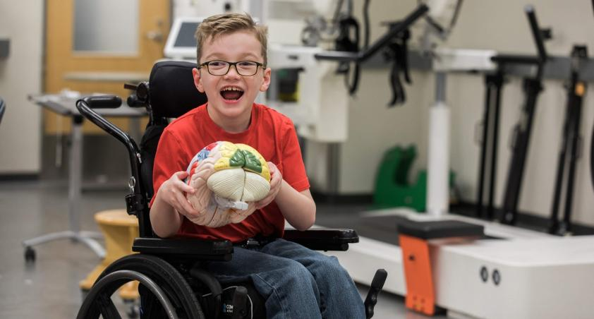 Client in a wheelchair playing with a brain toy