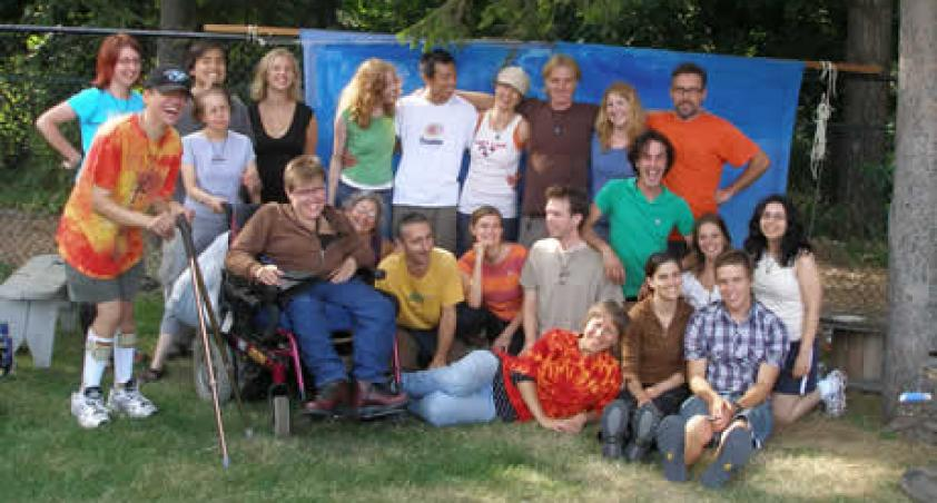 A group of staff, children and youth, including one in a wheelchair, standing by a fence.