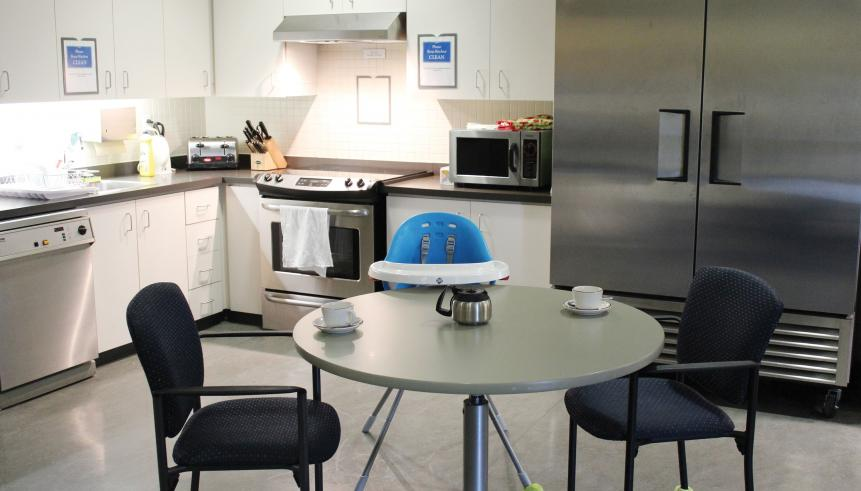 Communal kitchen area with dining table, dishwasher, sink, stove, and fridge