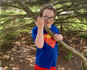 Wesley in a Superman shirt holding up a large branch.