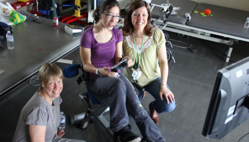 Two female scientists with a young girl using the Exergame bike