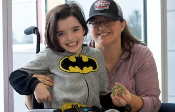 Girl wearing batman shirt in wheelchair with mom holding a clay art piece